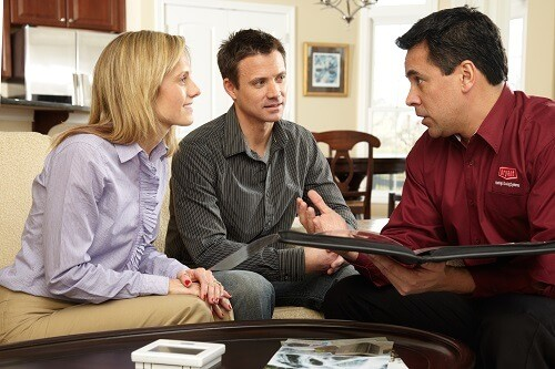 adult couple meeting with HVAC contractor