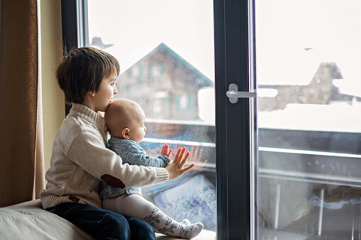two young kids looking out window