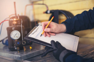 HVAC maintenance technician making notes about system
